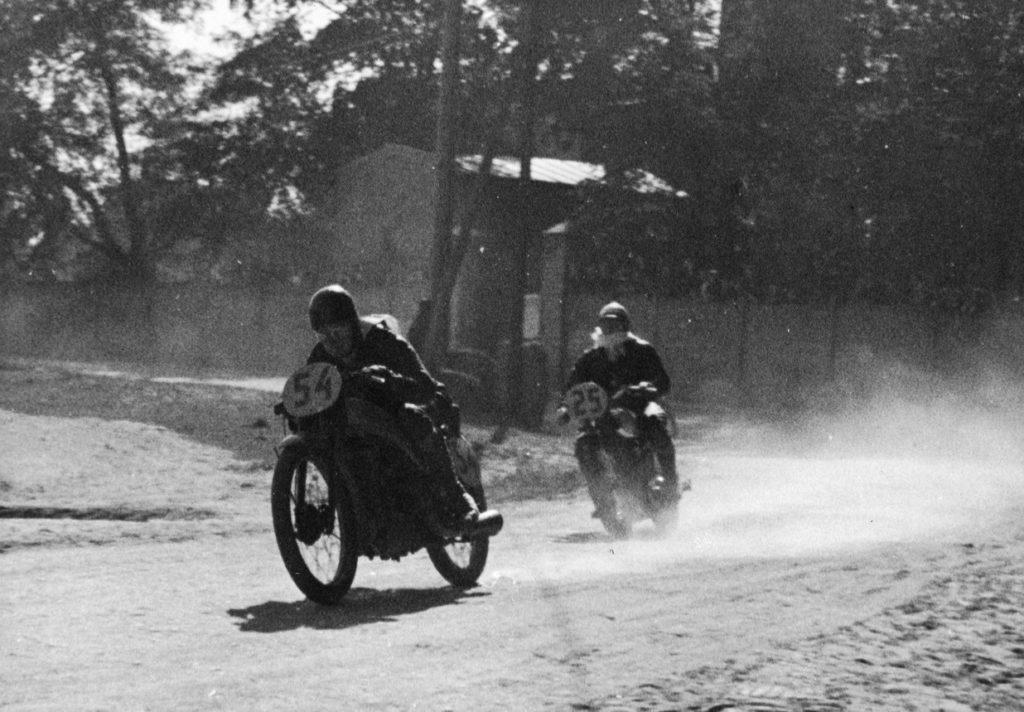 Na uliczkach Rudy. Jako pierwszy jedzie zawodnik niemiecki F. Nowotny na motocyklu Puch, za nim z nr 25 Wacław Ujczak z Legii na Sarolei