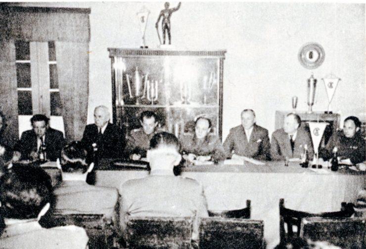 Zdjęcie zamieszczono w księdze Legia 1916-1966, gdzie błędnie je opisano, jako zebranie aktywu w 1966 r. Nie mogło być jednak w podanym okresie zrobione, ponieważ kilka osób przedstawionych na fotografii już wówczas nie żyło, lub nie działało w klubie. Nie istniał też wówczas CWKS (emblematy na proporczykach). W rzeczywistości zdjęcie przedstawia zebranie Sekcji Piłki Nożnej w świetlicy klubowej 26 stycznia 1957 r. i moment reaktywowania WKS Legia.  Za stołem zasiadło wówczas trzech przedwojennych Legionistów: Ziemian(niewidoczny), Mielech(6 od prawej) i Nowakowski(3 od prawej). Dwóch wojskowych w środku to płk. Malczewski (obok Mielecha) i  płk.Noworyta.